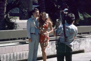 Japanese tourist taking pictures with a female in Aloha attire