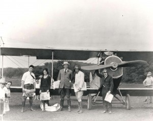 Photo of Charles Fern standing in front of a single propeller plane