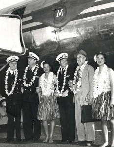 Pilots being welcomed with leis in front of an aircraft