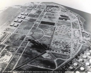 The water tower, paved roads, underground power, family housing, Bishop Point dock, hangars, Base Operations, apron and taxiway are in place, November 17, 1938. The railroad has been moved to Hangar Avenue and men continue to live in tents.
