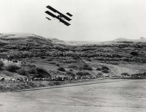 As the biplane with its gigantic wings swept over the grass field and rose into the air there was a general whoop of exultation and spontaneous applause from spectators.