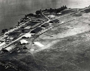 Luke Field on Ford Island with DH-4 and JN-4/6 aircraft lined up. At lower left are aircraft packing crates. Round spot on field is compass rose, 1919-1921.