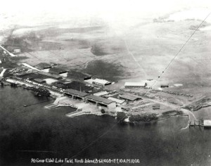 Luke Field on Ford Island with DH-4 and JN-4/6 aircraft lined up. At lower left are aircraft packing crates. Round spot on field is compass rose, c1919-1921.