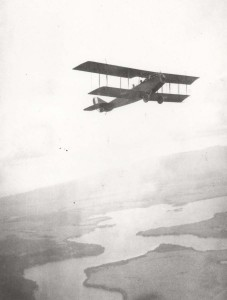 Biplane in flight over Pearl Harbor, 1920s.