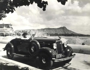 1935 Chevrolet convertible with Diamond Head and Waikiki Beach in the background.