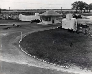 Wings at the entranceway flanking the gatehouse of Hickam Field were in place in 1937 but not yet painted and a perimeter fence had been installed. The original concrete gate portals still remain today, and were moved back to their present location in April 1978.