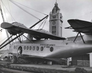 Inter-Island Airways. A Sikorsky S-43 is unloaded at Honolulu Harbor. Aloha Tower is in the background.