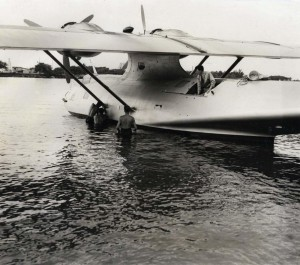 Guba flying laboratory plane. When the plane landed in Honolulu it almost ran afoul of concrete ramp at the end of the seaplane landing. Here are American sailors shoving her nose around from the dock to save a crack up.