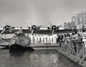 Patricia Kennedy, in the bow of plane, christens the Pan American Hawaii Clipper with coconut water, at Pearl Harbor. May 1936