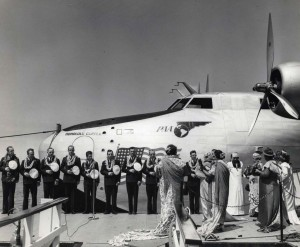 Helen Poindexter christens the Pan American Honolulu Clipper with coconut milk, dipping the fluid from a shell held by a member of the one-time royal court, then casting it to the four winds before touching the plane. 1939.