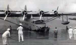 Pan American Clipper ship is assisted into hangar at Pearl Harbor by sailors.