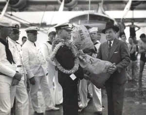 R.O.H. Sullivan, executive officer of Pan American Clipper, hands the first sack of air mail to John H. Wilson, U.S. Postmaster at Honolulu. April 20, 1935.