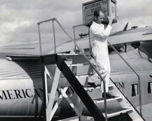 J A Brooks, PAA employee, carries first RCA Victor radio set from Pan American Clipper.