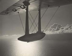 Sunset in the American tropics as Pan American's U.S. mail plane wings into Honolulu, 1930s.