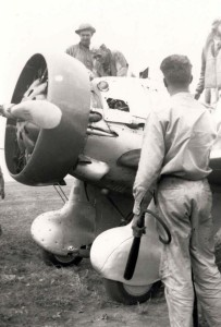 P-26 from Wheeler had a flash fire on start up at Morse Field, Hawaii. Squadron commander surveys damage. Pilot is wearing a Mae West. Someone had to stand on left wing and crank the engine with a hand crank to get it started, 1941.