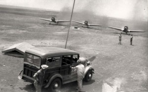 P-36s from Wheeler Field taxiing to gas pit at Morse Field, Hawaii, to refuel. Shown is a 1934 Chevy station wagon. The small roof covered the gas system segregation, 1941.