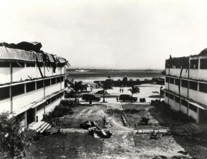 Looking out toward Hangar Avenue and the flight line from the courtyard between heavily damaged Wing E and Wing D of the big barracks at Hickam Field, December 7, 1941.