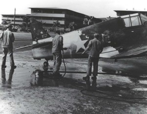 Ground crew members wash P-40 aircraft fuselage at Hickam Field, 1940.