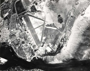 Hickam Field from 22,500 feet. Drainage canal from apex of runway and alluvial fan drainage at lower center. New railroad tracks at lower right, with old track still visible. Post exchange, clinic, officer's club, additional NCO and officer's quarters, warehouses, and engine shops, September 21, 1941.