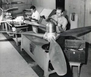 Hawaiian Airlines, March 1949. Mechanics work on propeller blades.