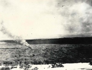 A downed Navy Scout Bomber Douglas (SBD) burns in Ewa as Japanese planes fly overhead, December 7, 1941.