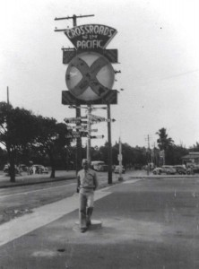 Soldier stands in front of Cross Roads of Pacific sign at Kau Kau Korner restaurant, Honolulu, 1940s.