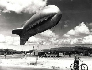 Barrage balloon crew at Fort Kamehameha in World War II. The balloon ascends slowly while the passersby watch with interest.