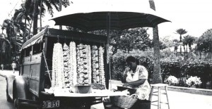 A lei maker sells her lei from the back of her vehicle. Similar vehicles lined Lagoon Drive on the road to Honolulu Airport during the 1940s and 1950s until permanent lei stands were built for the vendors.