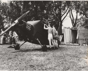 "Members of the 163rd, Liaison Squadron, 10th Army, dismantling Vultee L-5 Sentinels at Schofield Barracks, March 16, 1945. Note marking ""U High Flyer"" sponsored by the students at University High School, Honolulu."