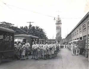 The first detachment of WACs to be in the Pacific Theater are loaded into buses at Aloha Tower for transfer to housing units, 1940s.