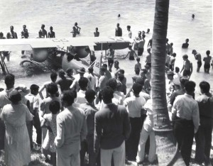 Bathers rescue a U.S. Army airplane from the surf after its crash due to motor failure. The pilot was uninjured and swam to a small fishing boat nearby.