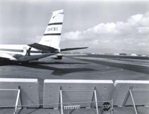 Qantas Airlines at Honolulu International Airport near blast fence, 1950s.