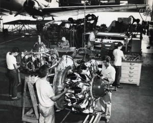 Hawaiian Airlines mechanics work on engines in shop at Honolulu International Airport, 1950s.