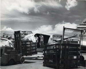 Cargo is loaded onto a Hawaiian Airlines plane at Honolulu International Airport, 1950s.