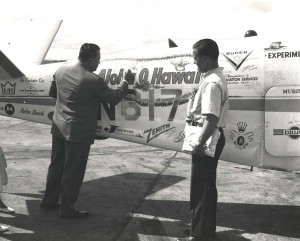 Col. Cholermahai Charuvastr, left, the Tourist Organization of Thailand's Director General, signs his name on the Bonanza fuselage while Captain Banfe looks on.