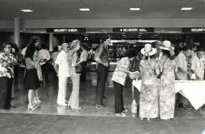 Visitor Information Program staff assist passengers through security checkpoint at Honolulu International Airport, 1980s.