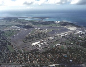 Hickam Air Force Base, Hawaii, as viewed from Pearl Harbor, looks makai with HNL's reef runway in the background, 1986.