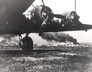 B-17 frames the devastating results from Japanese attack on Hickam Field, December 7, 1941. The smoke in the background is from USS Arizona which Japanese bombed. The B-17s arrived at Hickam the morning of the attack.