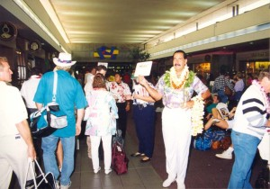 Photo of a greeter welcoming an arriving passenger to Honolulu