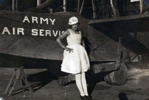 A woman poses in front of a Curtiss Model G Army Air Service plane, 1914.