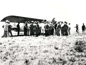 A crowd gathers around the Dole Derby winner Woolaroc after it came to a stop at Wheeler Field's grassy runway, August 16, 1927.