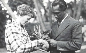 Honolulu Sheriff Duke Kahanamoku shares a pineapple with Amelia Earhart, January 2, 1935 at the Royal Hawaiian Hotel.