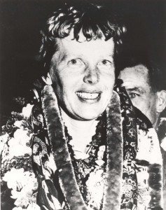 Amelia Earhart wears a lei upon arrival at Wheeler Field, Oahu, from California, March 18, 1937. She was pleased that the first leg of her east to west global flight attempt had been successful.