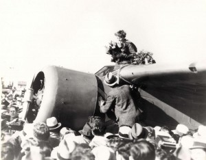 Amelia Earhart receives a bouquet in the cockpit of her plane after landing at Oakland Field, California, on January 12, 1935 after her flight from Hawaii.