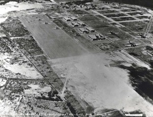 A formation of Martin B-12 and Douglas B-18 bombers over Hickam Field with some roads paved. The Diamond Head extension of the taxiway was begun by grading equipment and the railroad is in place to the left of the taxiway, June 18, 1938.