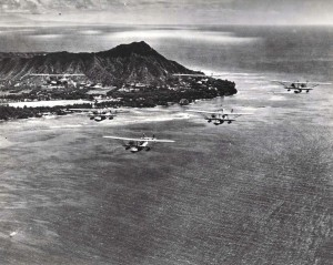 U.S. Navy bombing planes fly past Waikiki with Diamond Head in the background.