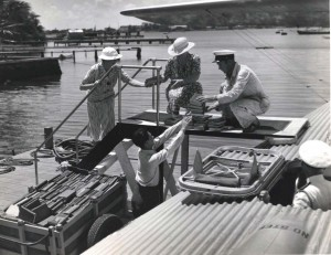 Library of Hawaii and Pan American Airways officials load books on the China Clipper for delivery to Wake and Midway Islands. June 1936.