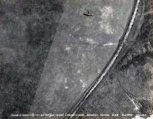 U.S. Army Air Corps camouflaged bomber flying over plowed ground, January 17, 1933.