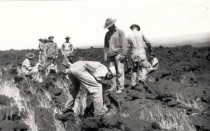 Detail is prepping a site on a lava flow at Morse Field, Hawaii, to lay out a 100-foot diameter circle for a bomb target. Cans of water and bags of lime were taken 700-feet down a goat path carried on the backs of the men, c1940-1941.
