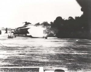 Smoke billows from burning B-17 on Hickam Field flight line, December 7, 1941.